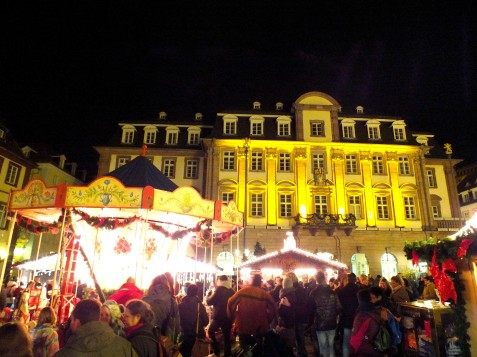 The town hall shines in a golden glow behind one part of the market